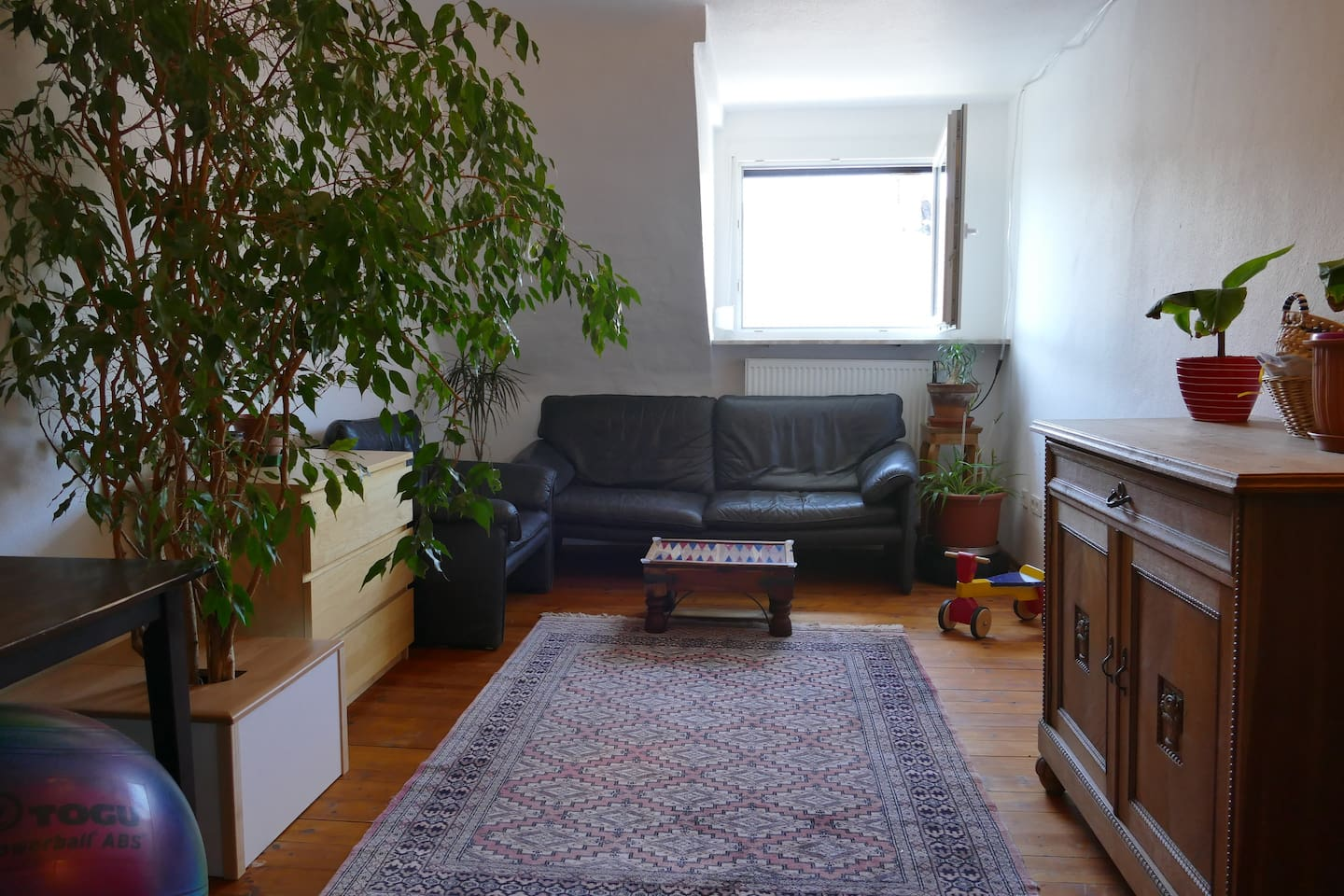 The living room, with babyproof plant pots and a second desk space