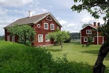 Gården Jon-Anunds i Järvsö med utsikten av Ljusnan i bakgrunden. Bilden visar gammelgården 1850-tal till vänster och boningshuset 1805-tal till höger.