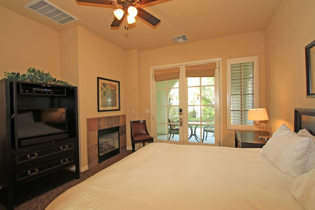 King bed with flat screen TV with french doors opening to patio