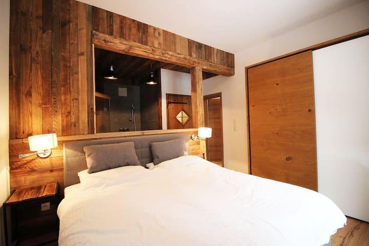 Masterbedroom mit Boxspringbett und ensuite Badezimmer