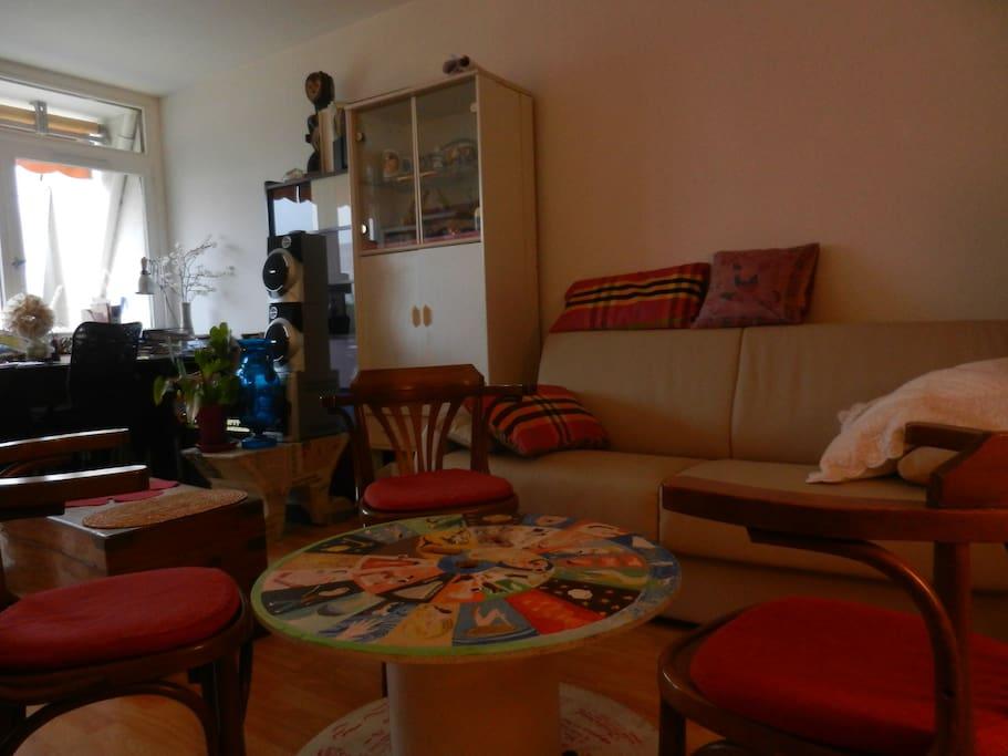 Un salon chaleureux et pratique avec un confortable canapé-lit pour deux.