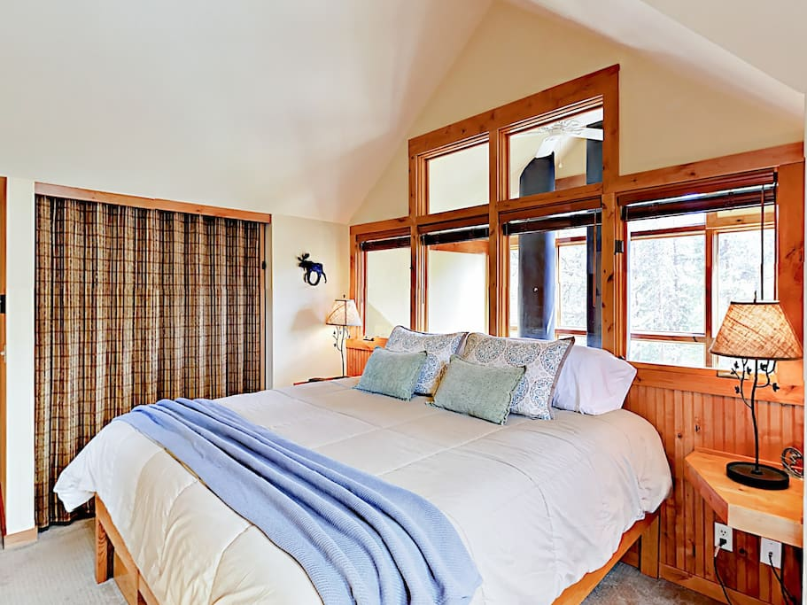 The master bedroom features a king bed and windows to the main living area below.