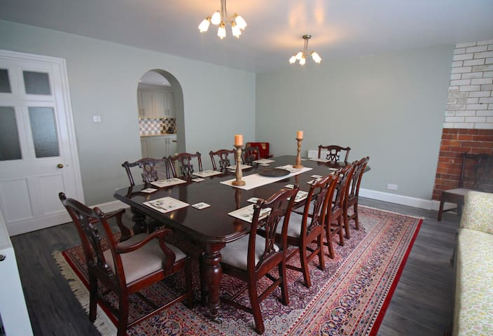 Our dining room has a 10 seater mahogany table.  The exposed tiles show the history of the building and its previous life as the butchers shop for the village.