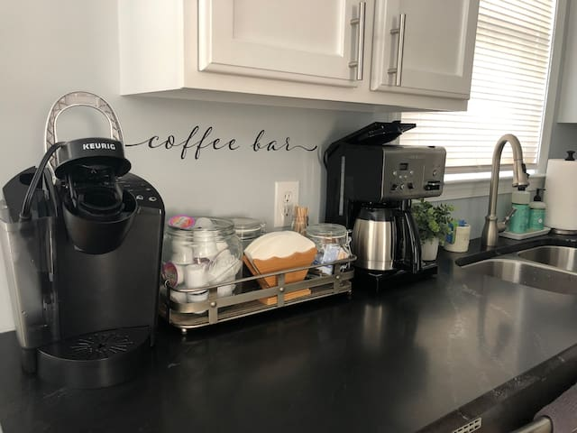 Coffee Bar with a Keurig K-Cup Maker, Traditional Full Pot Coffee Maker and a Hot Water Dispenser fully stocked with all amenities.