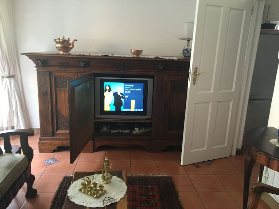 TV with DSTV and video player. The door on the right leads into the kitchen.