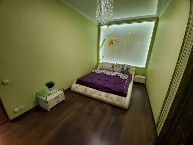Уютная спальня с большой двухспальной кроватью и выходом на балкон.