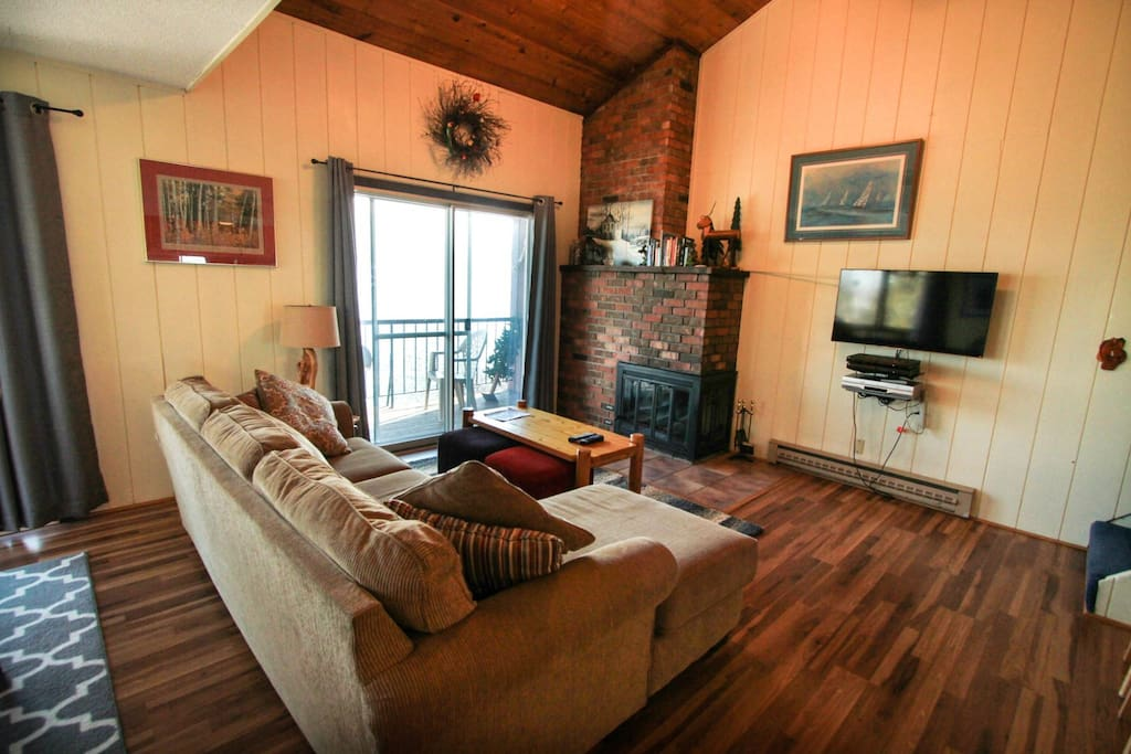The living room features a brick fireplace and flat screen TV.