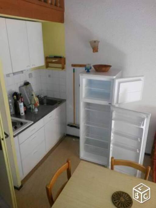 Le coin cuisine et son grand réfrigérateur permettant de stocker les courses de la semaine.