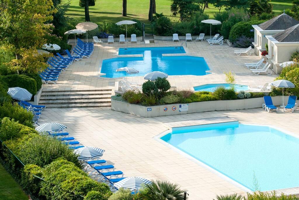 Les deux piscines dont une chauffée avec transats et parasols