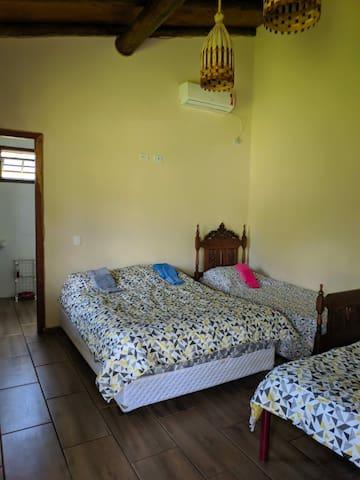 Quarto suite com duas camas de casal e uma cama de solteiro.