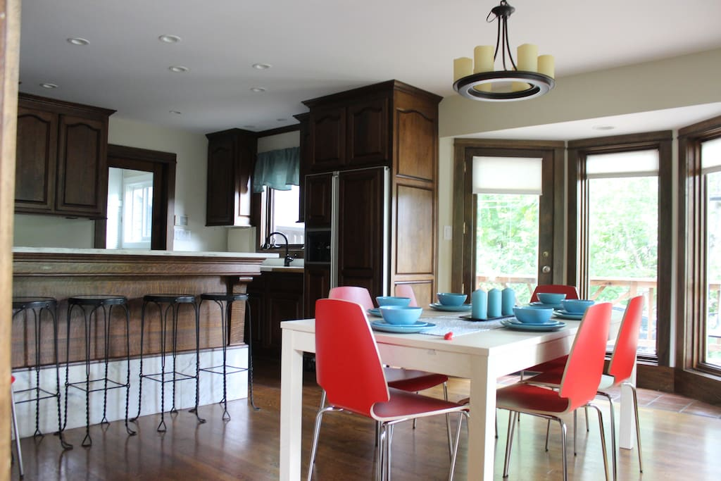 Dining room features extendable table with extra chairs as well as a converted soda fountain countertop and barstools.