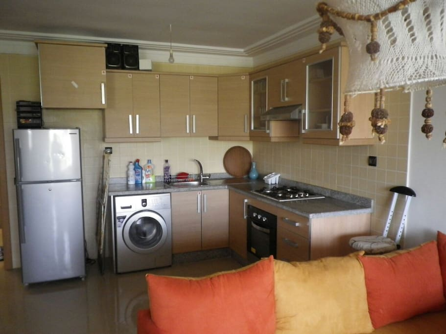 Fully equipped kitchen with washing machine, oven and range.