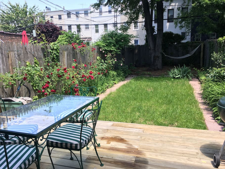 Private backyard features a wooden deck with charcoal grill, vintage wrought iron table and chairs and even a hammock! Perfect for a picnic or a nightcap under the Brooklyn sky!