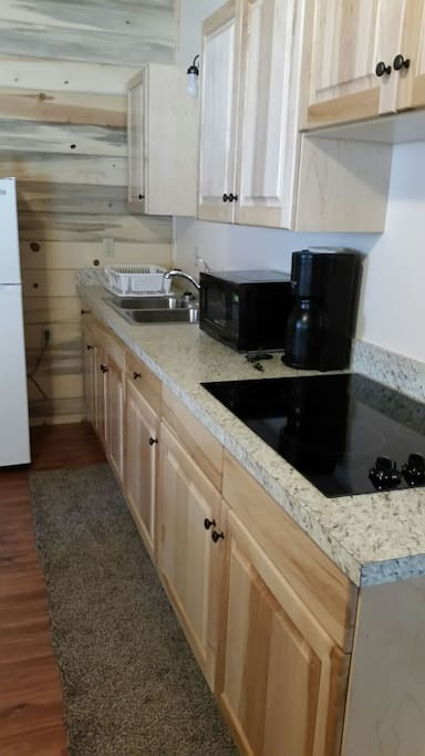 Kitchen with microwave, coffee pot, and stove top.