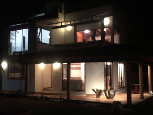 Vista de la casa con iluminación nocturna.