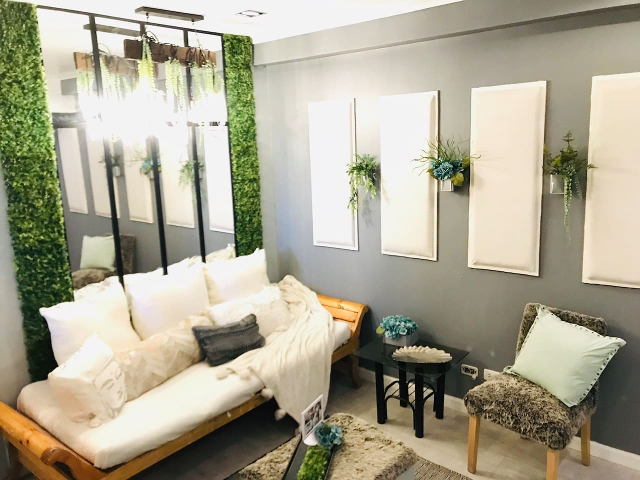White padded panels to serve as noise reduction are custom made with floor to ceiling mirror to reflect a window with lush permanent botanical greens. Sleigh-day-bed with accent pillows and chair blanket with blue hydrangeas to accent the room.