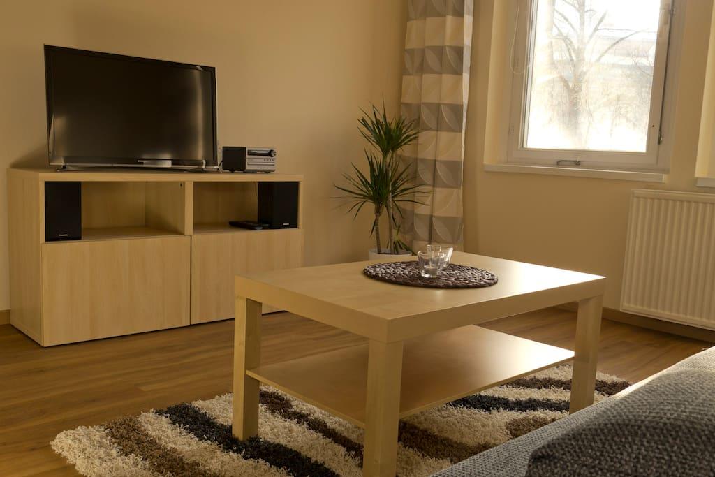 32Zoll Flat TV und VDSL, Couchtisch, Couch und ein Esstisch erwarten Sie im hellen Wohnbereich.