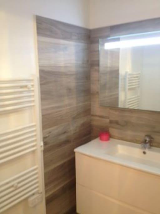 salle de bains avec baignoire et sèche serviette neuve