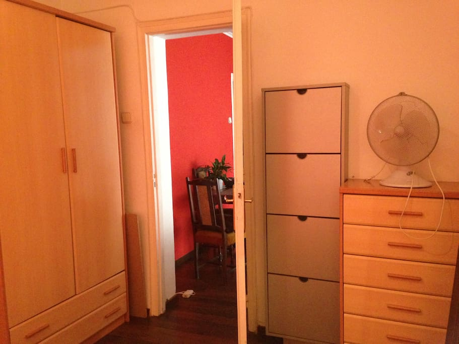 Large wardrobe, drawers and a fan in the room.