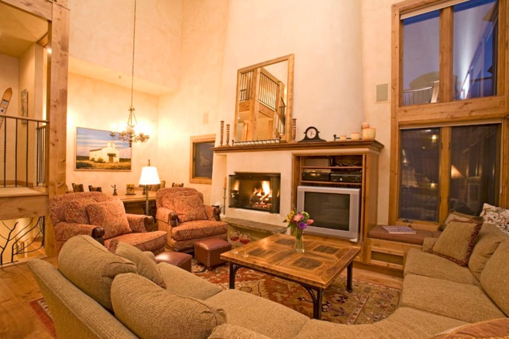The great room, with its fireplace, TV, and ridiculously high ceilings, is where everyone will want to be.
