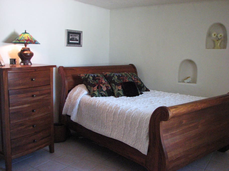 Oversized master bedroom with mahogany sleighbed, highboy and large mirror. View of fields and mountains,  private closet. Bose CD a.m./f.m. stereo alarm (behind photographer)
