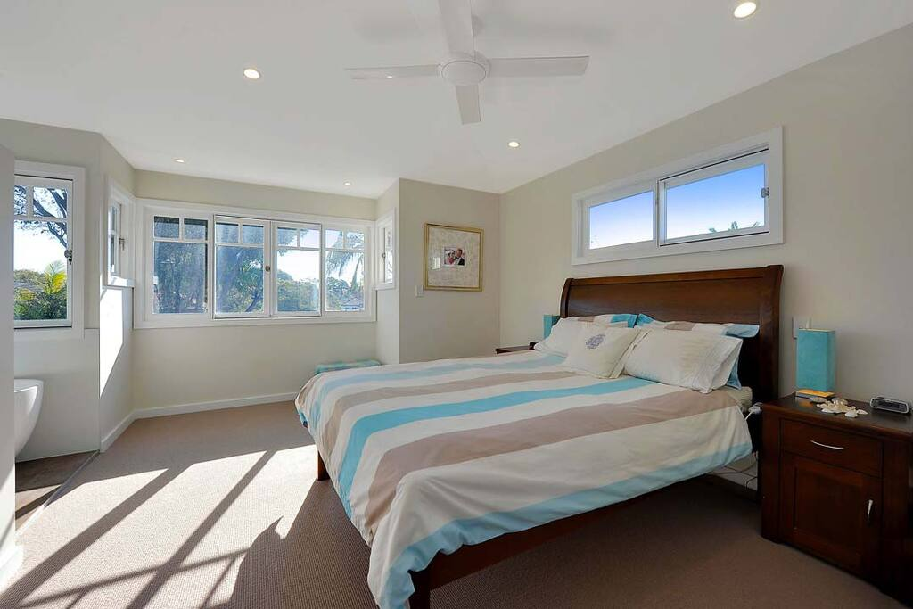 Master bedroom with Queen bed, overlooking rear sunny garden (with ceiling fans, bedside tables, walk-in robe, open ensuite bathroom adjoining)
