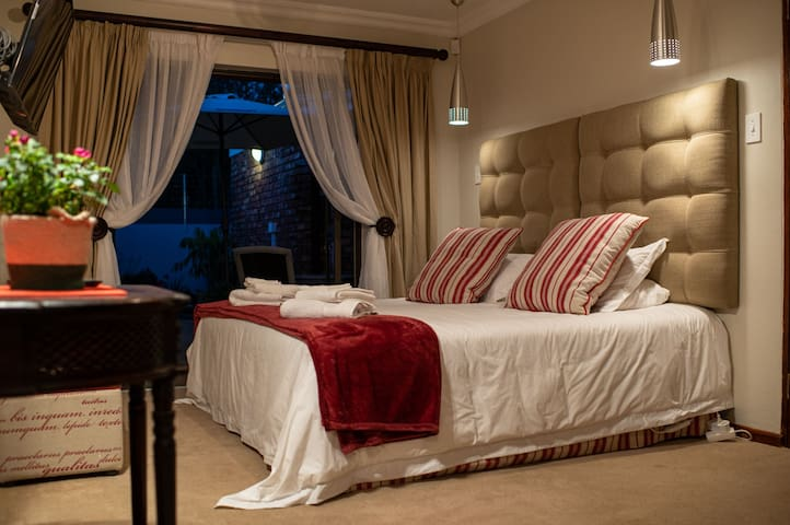 Main On-suite Bedroom with Kingsize Bed and Entrance to little garden and patio set
