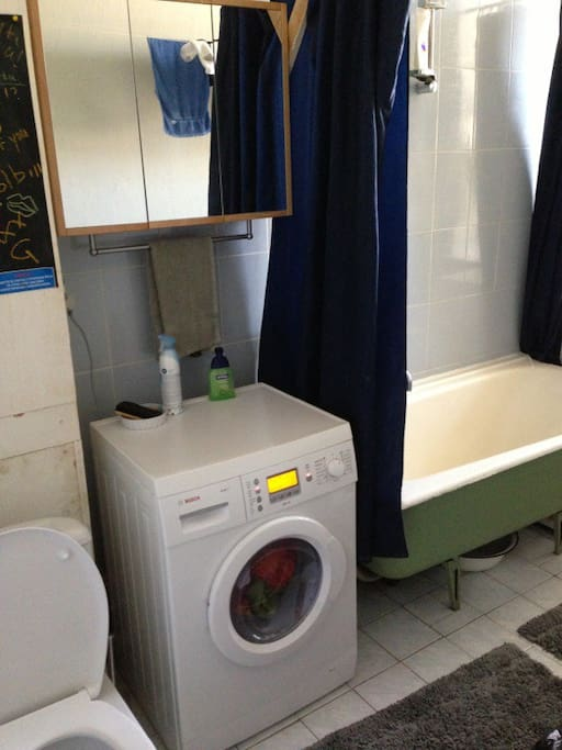 bathroom with tub and washing machine with dryer function