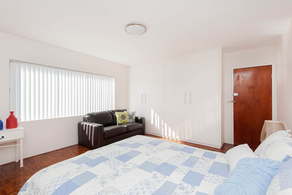 Spacious for a studio, offers bedding for up to 2 adults and 2 kids with a queen bed and a leather sofa bed