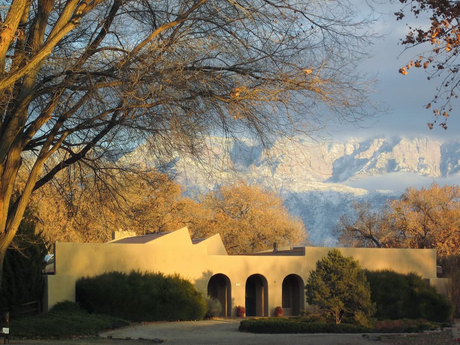 Adobe home with a snow covered Sandia Mountain in the background