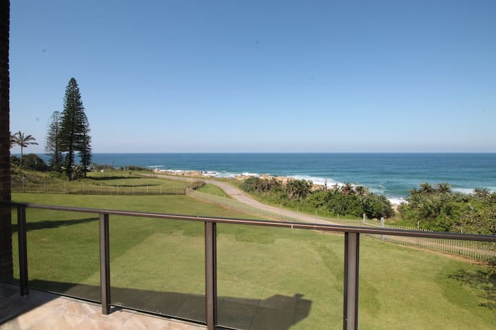 View from the balcony overlooking the garden and beach