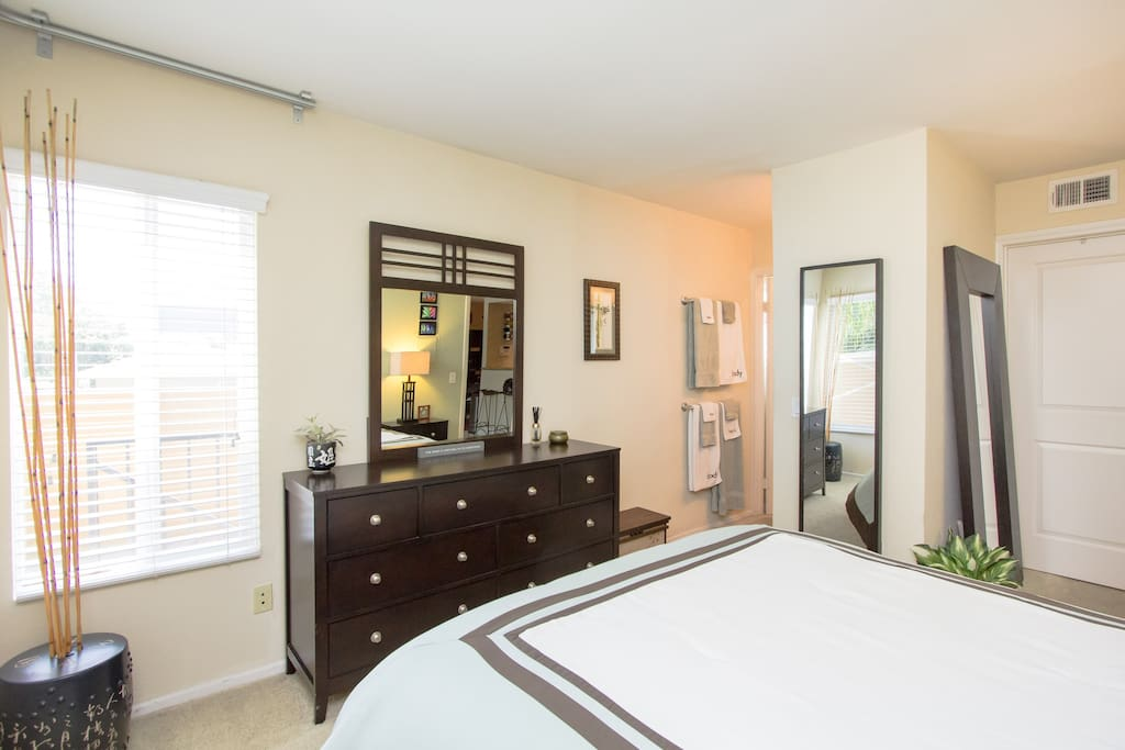 Unpack in the full chest of drawers at the foot of the bed so you feel right at home! This is the view looking in toward the private bathroom. The closed door is a huge walk-in closet, which you will also have full-access to.