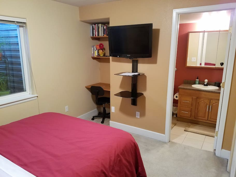 Wall-mounted television with cable, desk area, and bathroom entrance.