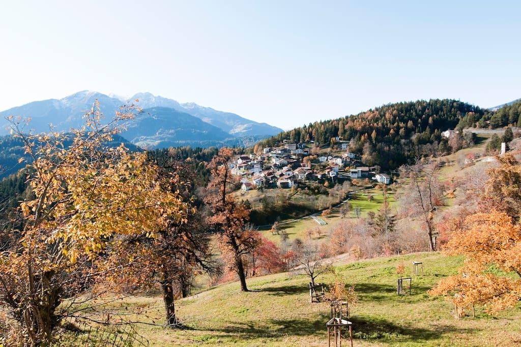 Garten und Sitzplatz mit Tischgarnitur, Smoker und Liegestühlen an einem sonnigen Hang mit Blick in die Berge