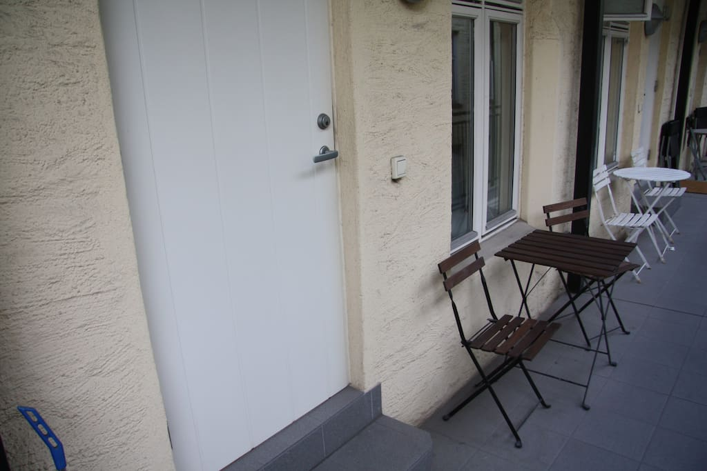 The front door with table and two chairs that belongs to the apartment.