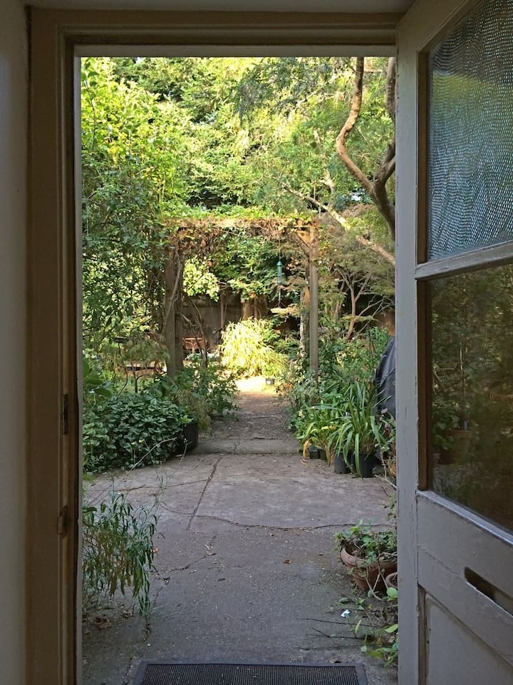 Private door in the rear of the house opens to a modern day secret garden. Patio area for guests is off to the left along the driveway extension.