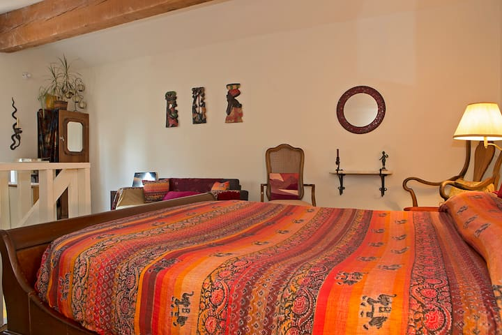 Comfy, sleigh bed.  African carvings on wall.