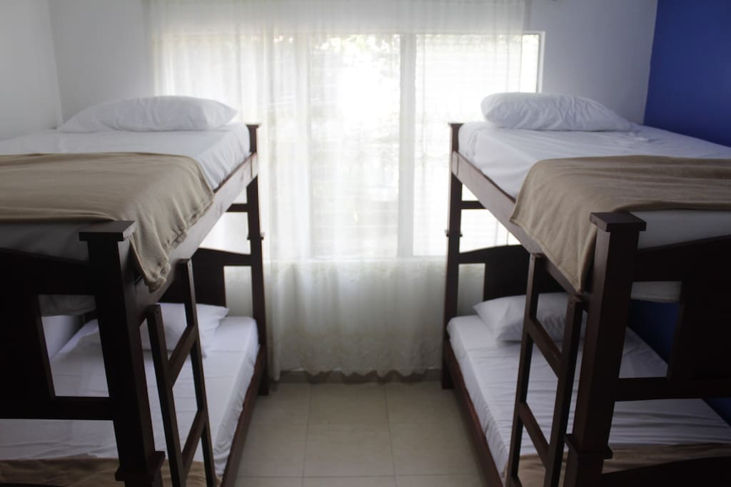 Habitación privada con 4 camas, fresca, con vista a la calle.