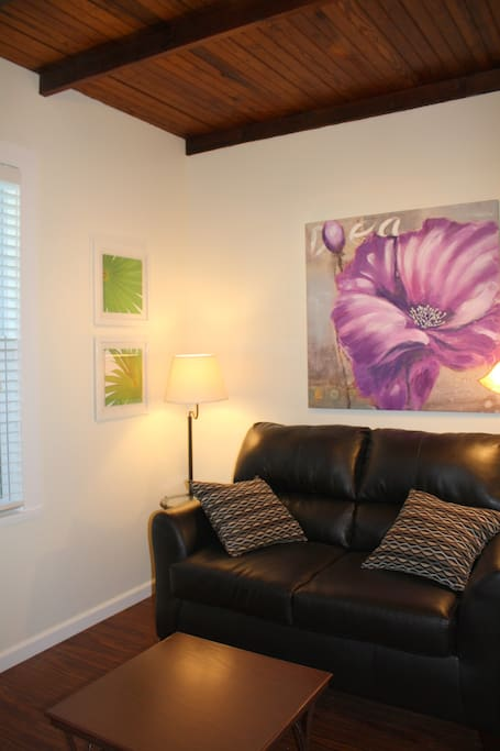 The living room has a large flat screen tv and leather loveseat for relaxing.
