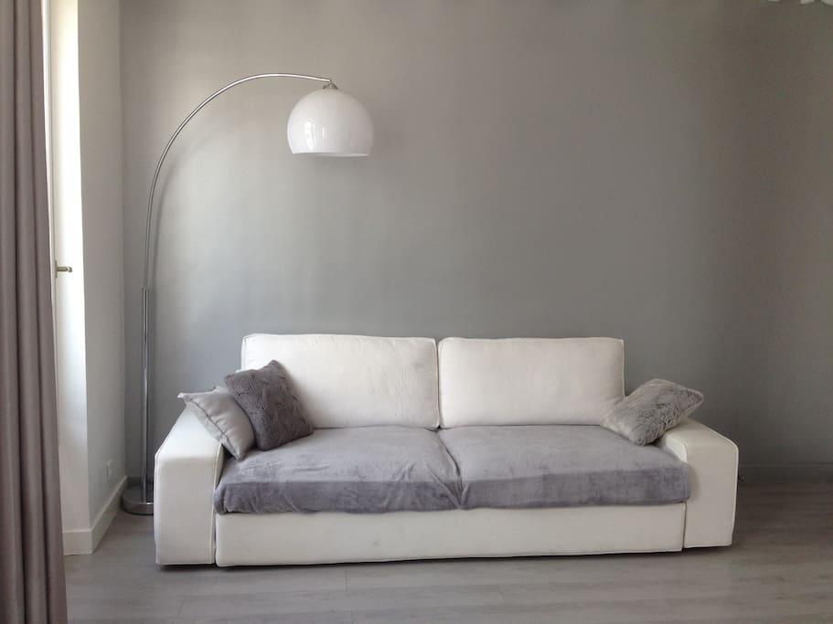 Salon lumineux et design avec grand canapé 4 places, TV