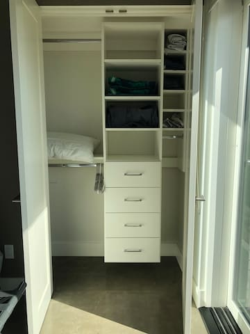 Organized closet with extra sheets and beach towels.  Also mirrored on exterior of doors