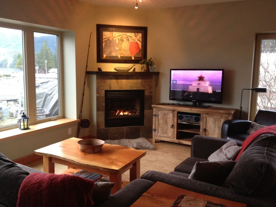 bright and cozy living room area open to dining, kitchen and balcony overlooking the boats in the small craft harbour