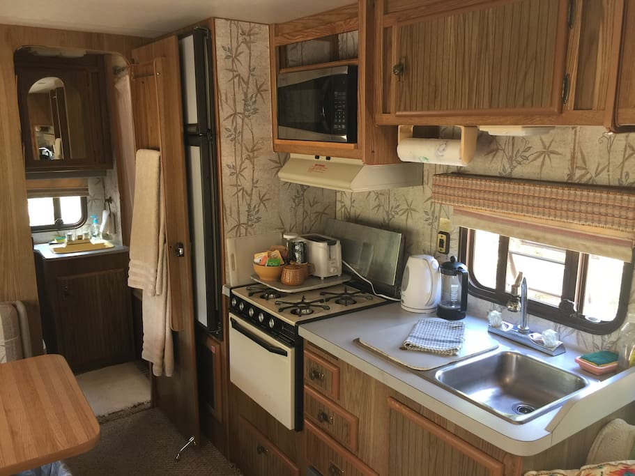 Fully stocked Kitchenette with fridge stove and sink, pots pans, dishes etc.