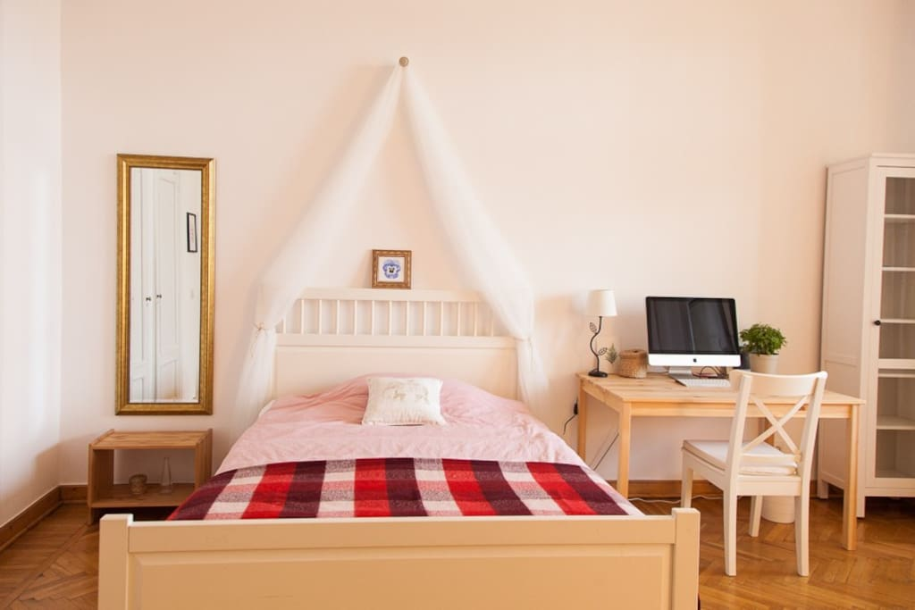 Большая двуспальная кровать с удобным матрасом.  Также есть рабочий уголок с деревянным столом, настольный лампой и шкафом для книг и документов.