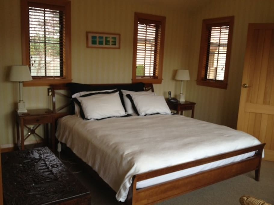 Tauhara King Room with ensuite with toilet, shower, twin basins, heated towel rail, hair dryer and complimentary toiletries. There is a walk in wardrobe and French doors out to a deck overlooking Mt Tauhara