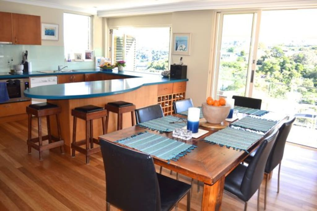 Open plan kitchen, dining and living space with large sliding doors to entertaining balcony overlooking pool and harbour foreshore.