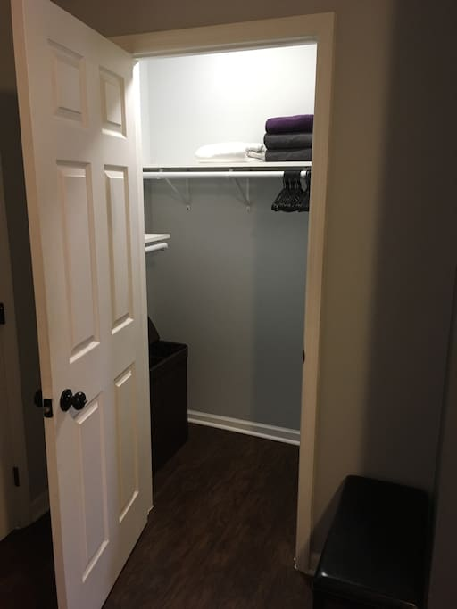 CLOSET: full walk in closet with fresh towels, hangers, and clothes hamper