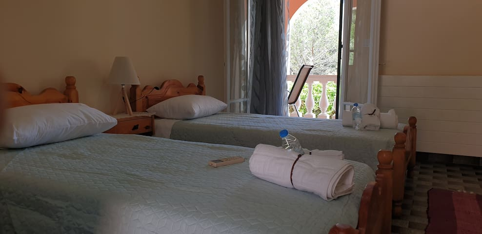 Bedroom with A/C,two single beds, towels and bottle of water