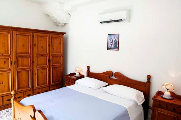 double bedroom with air conditioning and window overlooking the sea