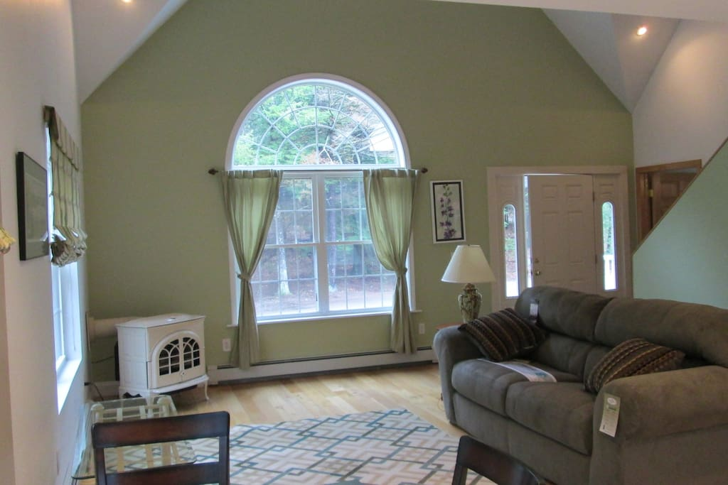 Spacious cathedral ceiling living room with gas stove.
